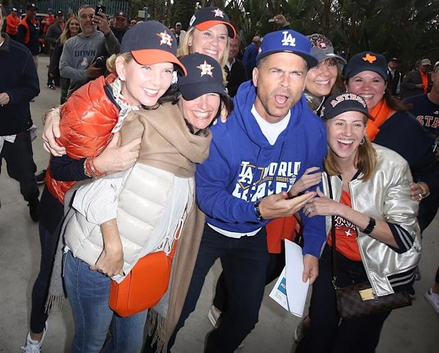 <p>Alhough he's a diehard Dodgers supporter, the actor stopped to take photos with a large group of Houston Astros fans before Game 6 of the World Series on Tuesday in Los Angeles. Lucky for Rob, his team came out on top, forcing a Game 7. (Photo: GICA/Backgrid) </p>