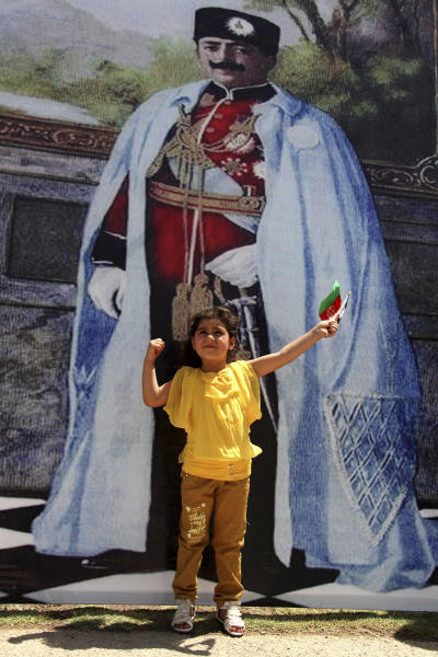 An Afghan girl poses for photos in front of a poster of King Amanullah in Herat province west of Kabul, Afghanistan, Monday, Aug, 19, 2013. Afghan officials mark the country's 94th independence day from Britain with a small military parade and folk festivals in the capital. (AP photo/Hoshang Hashimi)