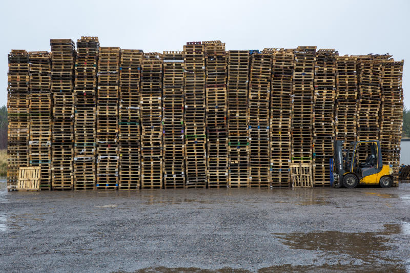A pallet truck parked in front of a large stack of wooden pallets on an industrial site near the M74 on the edge of Happendon Wood near Lanark, Scotland. (photo by Andrew Aitchison / In pictures via Getty Images)