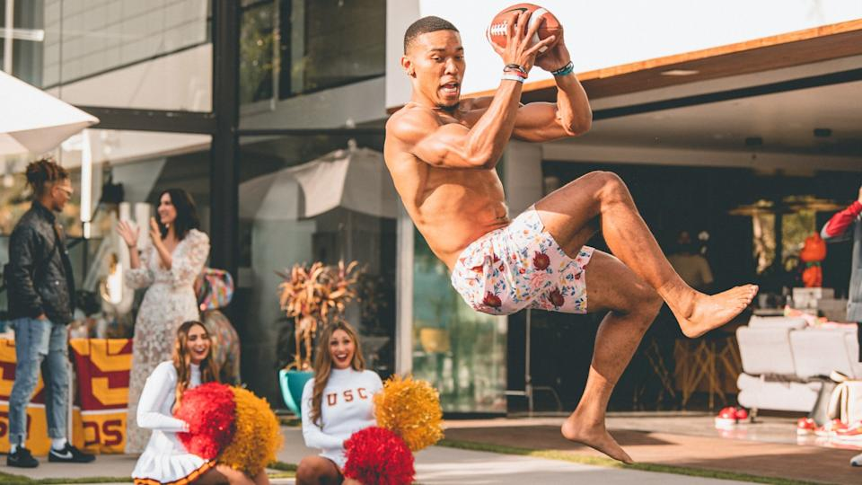 USC receiver Amon-ra St. Brown jumps into a pool at an event showing off the university's in-house creative lab.