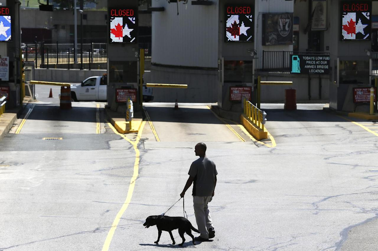 A dog is used by authorities to investigate a bomb threat at the Detroit Windsor Tunnel Thursday, July 12, 2012. The tunnel was closed to traffic after the threat was called in on the Canadian side, tunnel chief executive Neal Belitsky told The Associated Press. The call was made some time after 12:30 p.m. to the duty free shop on a plaza on the tunnel's Windsor side, tunnel executive vice president Carolyn Brown said. The underwater tunnel stretches about a mile beneath the Detroit River, which is one of North America's busiest trade crossings. (AP Photo/Paul Sancya)