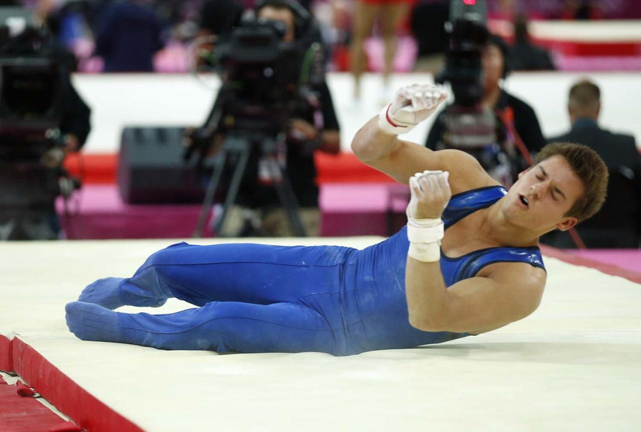 U.S. gymnast Samuel Mikulak falls during a performance on the horizontal bar at the Artistic Gymnastics men's qualification at the 2012 Summer Olympics, Saturday, July 28, 2012, in London. (AP Photo/Matt Dunham)