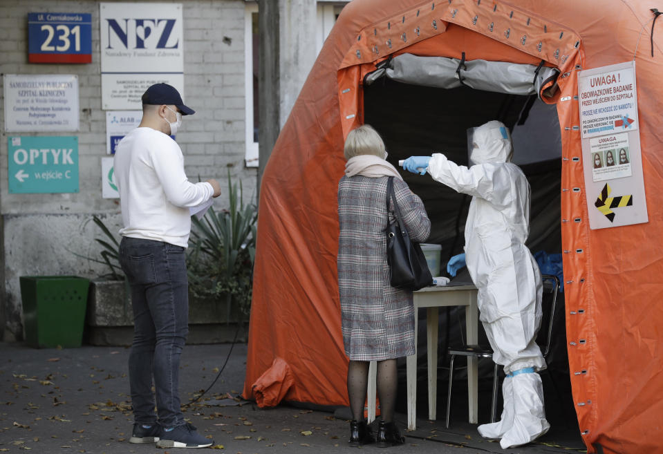 People arrive to be tested for COVID-19 in Warsaw, Poland, Thursday, Oct.22, 2020. With cases surging in central Europe, some countries are calling in soldiers, firefighters, students and retired doctors to help shore up buckling health care systems. Many faced a shortage of medical personnel even before the pandemic, and now the virus has sickened many health workers, compounding the shortfall. (AP Photo/Czarek Sokolowski)