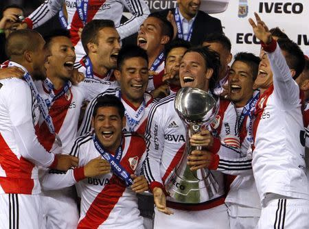 River Plate's players celebrate with the trophy after winning the Argentine first division soccer championship in Buenos Aires