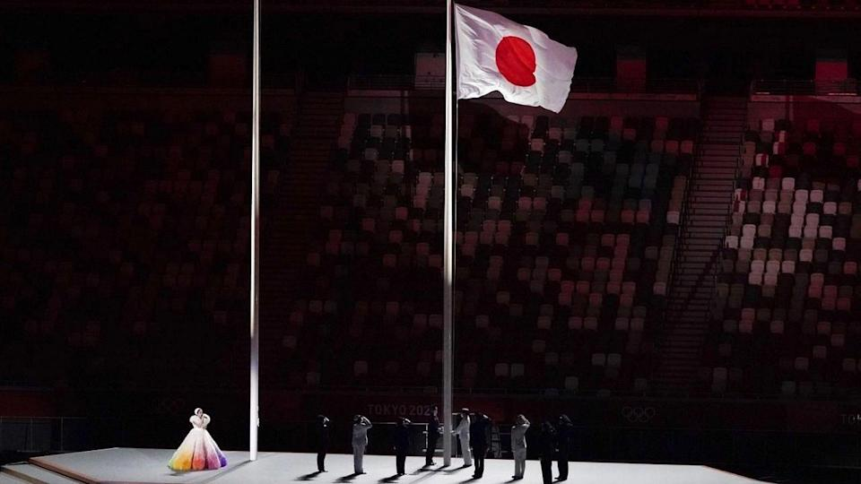 """<div class=""""paragraphs""""><p>Officials unfurl the Japanese national flag at the National Stadium on Friday</p></div>"""