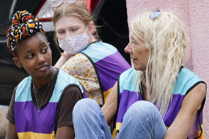 Veteran clinic escort Derenda Hancock, right, confers with younger defenders Asia Brown, left, and Ellie Rome, center as they wait outside the Jackson Womens Health Organization clinic parking lot for patients, Thursday, May 20, 2021, in Jackson, Miss. The clinic is Mississippi's only state licensed abortion facility. On May 17, 2021, the U.S. Supreme Court agreed to take up the dispute over a Mississippi ban on abortions after 15 weeks of pregnancy. The issue is the first test of limits on abortion access to go before the conservative majority high court. Their decision could mean more restrictions, and focuses on the landmark 1973 ruling in Roe v. Wade, which established a woman's right to an abortion. (AP Photo/Rogelio V. Solis)