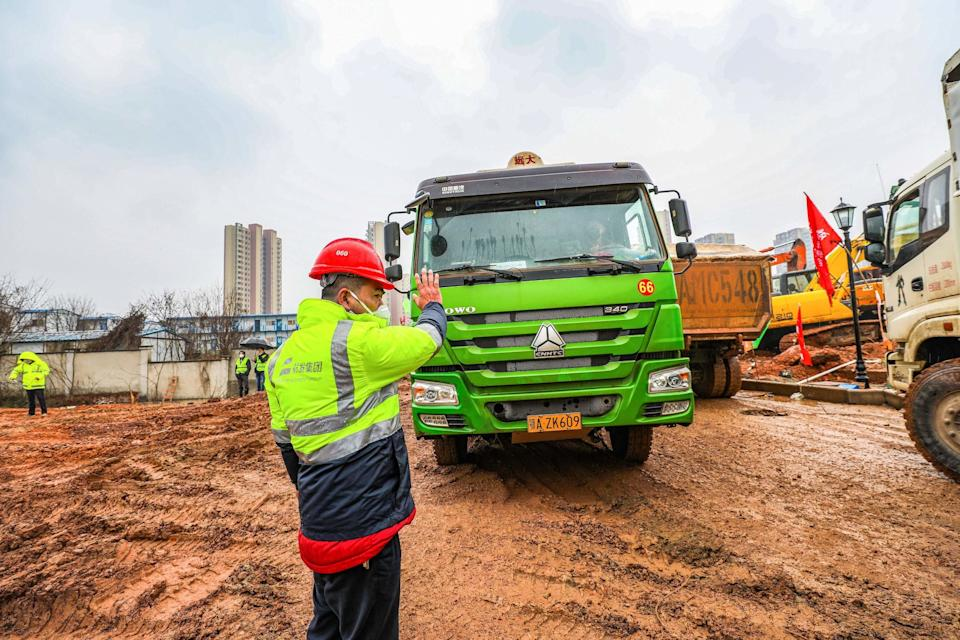 A worker controls the flow of trucks entering the site.