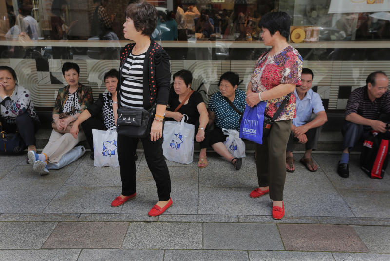 Chinese tourists take a rest in front of a department store in Tokyo Friday, June 28, 2013. Japan got a dose of upbeat economic news Friday when the government said industrial production rose 2 percent in May from April, the fourth straight monthly increase, while the most-watched consumer price index stopped falling for the first time in seven months. (AP Photo/Itsuo Inouye)
