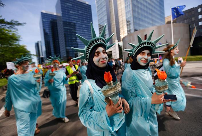 <p>Protesters dressed as the Statue of Liberty march during a demonstration in the center of Brussels on Wednesday, May 24, 2017. Demonstrators marched in Brussels ahead of a visit of President Donald Trump and a NATO heads of state summit which will take place on Thursday. (Photo: Peter Dejong/AP) </p>