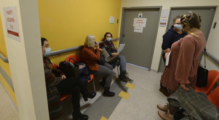 Polish teachers wait to be administered with their first shot of the AstraZeneca vaccine against the coronavirus in Krakow, Poland, Friday Feb. 12, 2021. As Poland began vaccinating teachers on Friday, many say they are unhappy that they are getting AstraZeneca vaccines against the coronavirus, rather than the Pfizer shots earmarked for health care workers and the elderly. Nearly a year into the pandemic, many Europeans and others globally are desperate to get vaccinated and return to normal life. But many don't want just any vaccine. (AP Photo/Czarek Sokolowski)