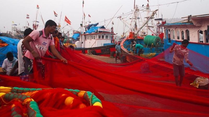 Fishers roll out a red purse-seine net in Mangalore, a major fishing harbour in southwest India.
