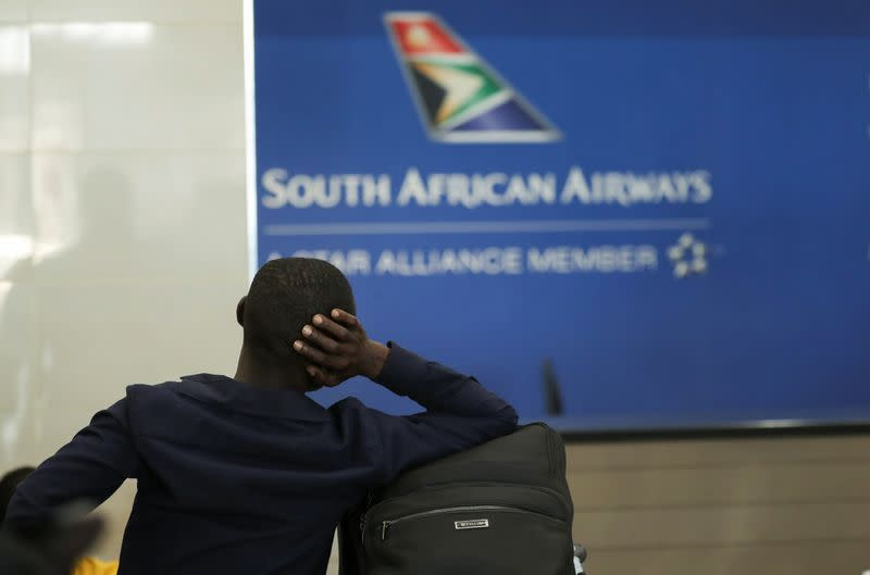 FILE PHOTO: A passenger is seen at the South African Airways (SAA) customer desk at the O.R. Tambo International Airport in Johannesburg