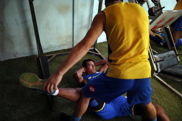In this Oct. 18, 2014 photo, Deportivo Capiata soccer player Jorge Paredes gets help to stretch during training in Capiata, Paraguay. After Capiata defeated Argentina's Boca Juniors in a first leg of the Copa Sudamericana, the team must face the Argentine juggernaut again on Thursday, Oct. 23 for the second leg. The winner goes to the quarterfinals. (AP Photo/Jorge Saenz)