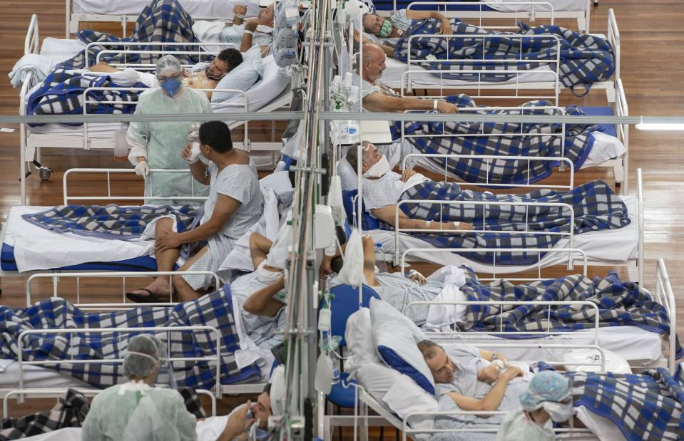 FILE - In this June 9, 2020, file photo COVID-19 patients lie on beds in a field hospital built inside a gym in Santo Andre, on the outskirts of Sao Paulo, Brazil. A new snapshot of the frantic global response to the coronavirus pandemic shows some of the world's largest government donors of humanitarian assistance are buckling under the strain and overall aid commitments have dropped by a third from the same period last year. (AP Photo/Andre Penner, File)