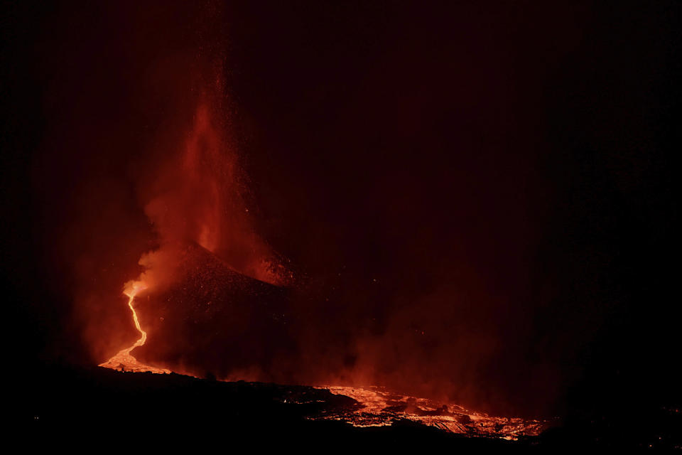 Lava spews from a volcano on the Canary island of La Palma, Spain in the early hours of Saturday Sept. 25, 2021. A volcano in Spain's Canary Islands is keeping nerves on edge several days since it erupted, producing loud explosions, a huge ash cloud and cracking open a new fissure that spewed out more fiery molten rock. The prompt evacuations are credited with helping avoid casualties but scientists say the lava flows could last for weeks or months. (AP Photo/Daniel Roca)