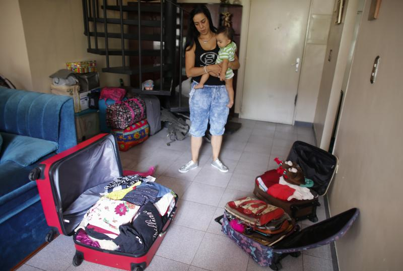 In this Oct. 31, 2019 photo, Yenika Calderon, 41, holds her 10-month-old baby Gael, while standing inside her apartment with suitcases packed with personal belongings to sell at a secondhand market, in Caracas, Venezuela. Deciding that it's time to abandon her crisis-torn homeland of Venezuela, Calderon hopes the money she makes will give her young family a fresh start far away in Spain. (AP Photo/Ariana Cubillos)