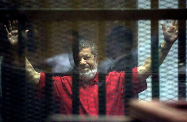 PHOTO: Former Egyptian President Mohammed Morsi raises his hands inside a defendants cage in a makeshift courtroom at the national police academy, in an eastern suburb of Cairo, Egypt, June 18, 2016. (Amr Nabil/AP, FILE)
