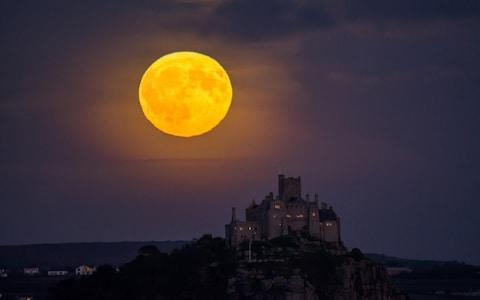 The full Harvest moon rises over St Michael's Mount in Cornwall - Credit: Simon Maycock / Alamy Live News