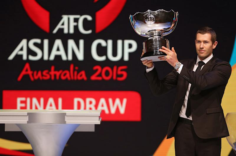 Australian soccer player Brett Emerton raises the trophy before the Asian Football Confederation draw for the 2015 Asian Cup at the Sydney Opera House ground in Sydney, Wednesday, March 26, 2014. Australia hosts the tournament that will be played in Jan. 2015. (AP Photo/Rick Rycroft)