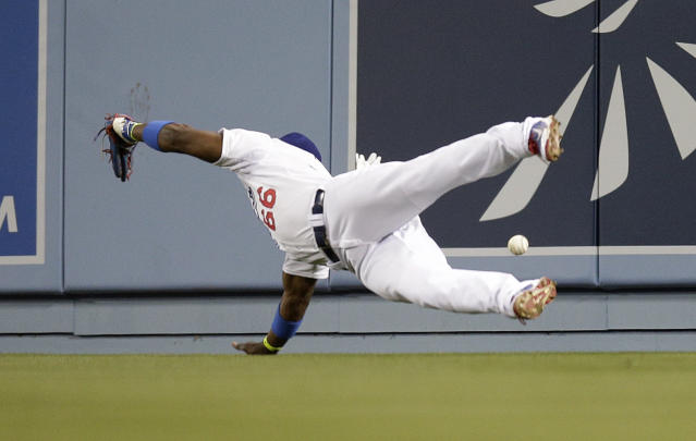 Los Angeles Dodgers right fielder Yasiel Puig can't make the catch on a two-run double by Philadelphia Phillies' Marlon Byrd during the fifth inning of a baseball game Thursday, April 24, 2014, in Los Angeles. (AP Photo/Jae C. Hong)