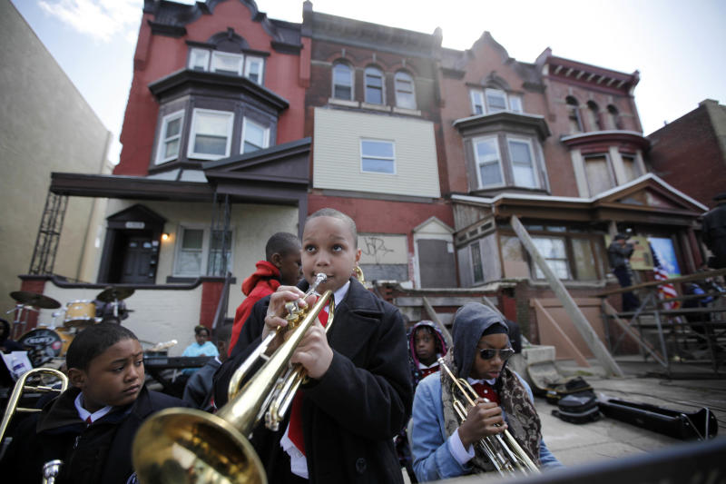 Students play music near the former home, third from left, of jazz musician John Coltrane Friday, April 13, 2012, in Philadelphia. Jazz lovers and cultural officials in Philadelphia are promoting a fundraising effort to save the run-down house. Coltrane lived in a rowhouse in the city's Strawberry Mansion neighborhood from 1952 to 1958. (AP Photo/Matt Rourke)
