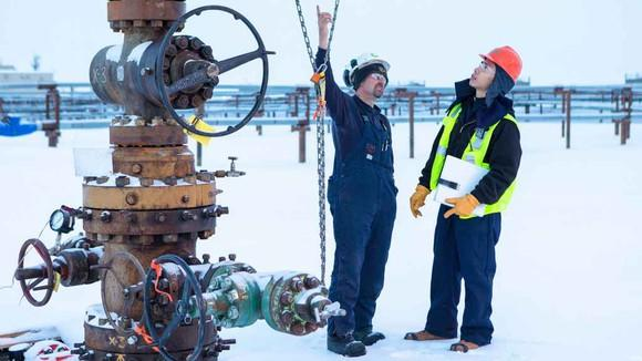 Two oil service workers standing near a wellhead in winter.