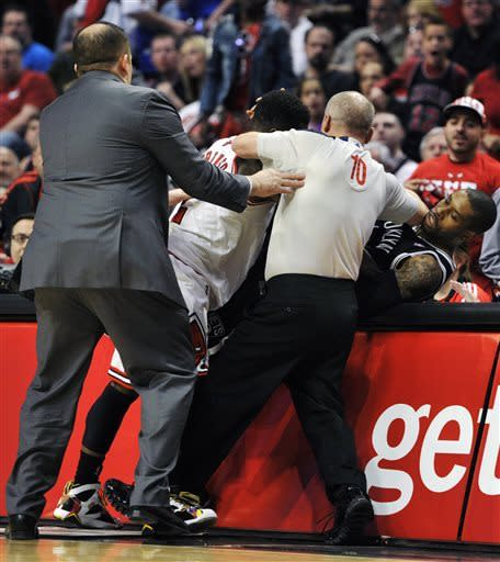 Chicago Bulls head coach Tom Thibodeau and referee Ron Garretson (10) try to break up a scuffle between the Chicago Bulls' Nate Robinson and Brooklyn Nets' C.J. Watson during the first half in Game 4 of their first-round NBA basketball playoff series Saturday, April 27, 2013, in Chicago. (AP Photo/Jim Prisching)
