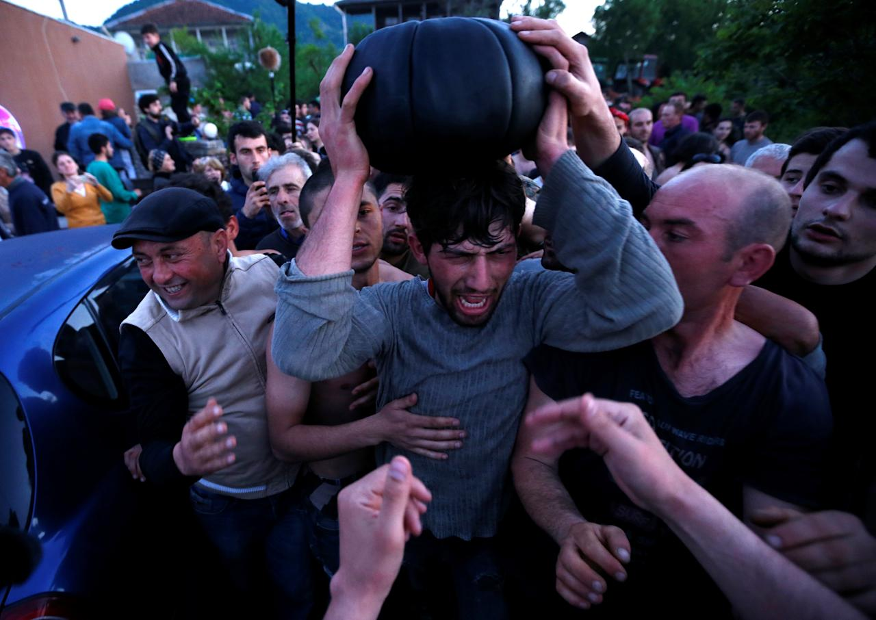 Winners celebrate after the annual Lelo match in the village of Shukhuti, Georgia, May 1, 2016. The villagers of Zemo (upper) Shukhuti and Kvemo (lower) Shukhuti have played the game every Easter Sunday for generations, with each side trying to carry the 16-kilogram ball to their end of the neighbouring villages. REUTERS/David Mdzinarishvili