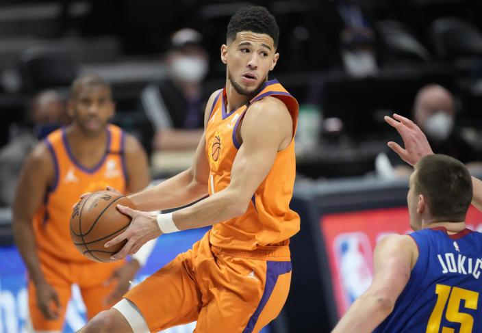 Phoenix Suns guard Devin Booker, front left, looks to pass the ball as Denver Nuggets center Nikola Jokic, right, defends in the first half of Game 3 of an NBA second-round playoff series Friday, June 11, 2021, in Denver. (AP Photo/David Zalubowski)