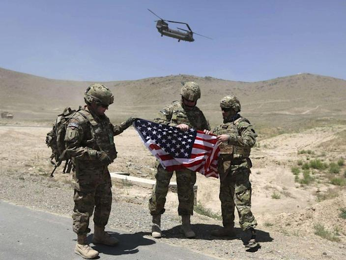 Nato soldiers stand with US flag as a Chinook helicopter takes off after a security handover ceremony at a military academy outside Kabul (Reuters)