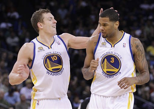 Golden State Warriors' David Lee, left, congratulates teammate Jeremy Tyler after Tyler scored against the Denver Nuggets during the second half of an NBA basketball game Saturday, April 7, 2012, in Oakland, Calif. (AP Photo/Ben Margot)