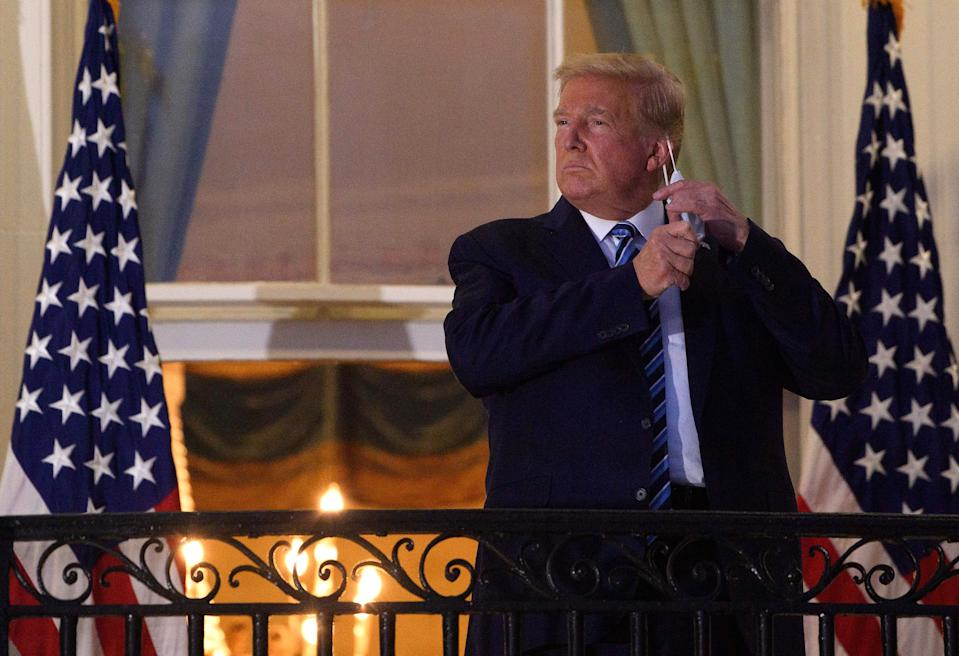 US President Donald Trump takes off his facemask as he arrives at the White House upon his return from Walter Reed Medical Center, where he underwent treatment for Covid-19, in Washington, DC, on October 5, 2020. (Nicholas Kamm/AFP via Getty Images)