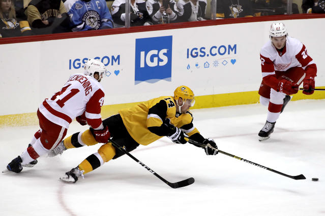Pittsburgh Penguins' Tanner Pearson (14) gets off a pass as he falls to the ice with Detroit Red Wings' Luke Glendening (41) defending during the first period of an NHL hockey game in Pittsburgh, Thursday, Dec. 27, 2018. (AP Photo/Gene J. Puskar)