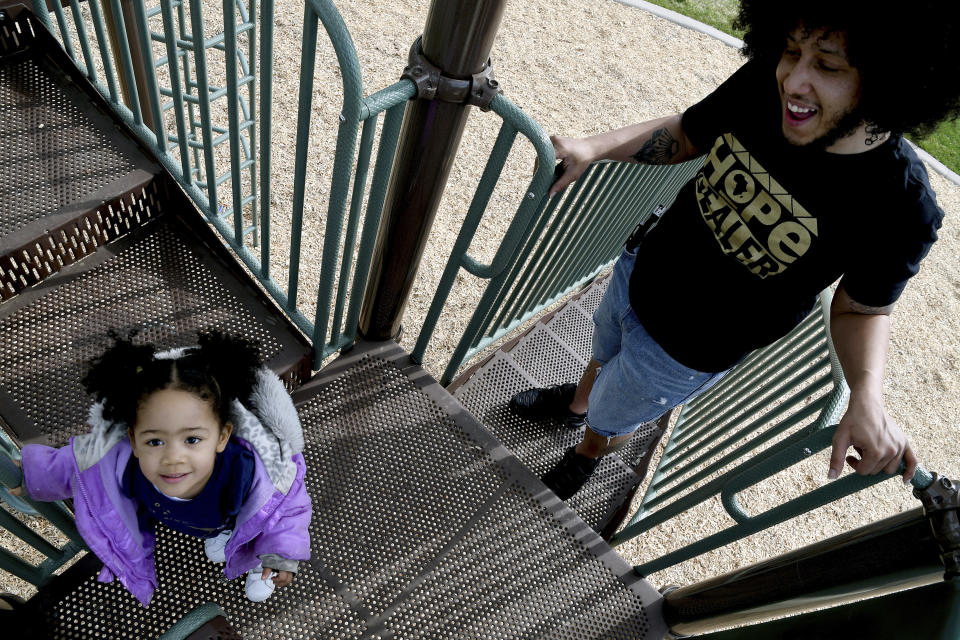 Michael Diaz-Rivera plays with his 2-year-old daughter Aria at a Denver park on Friday, April 23, 2021. Diaz-Rivera was pulled over in Colorado Springs, Colo. in 2006, and officers found two bags of marijuana in his car. After he was convicted of felony drug possession, he struggled to find housing, ran into hurdles while applying for federal student aid and was denied jobs. Now an elementary school teacher, he sees his future in a pot delivery business made possible by Colorado's marijuana social equity program, which is aimed at correcting past wrongs from the war on drugs. Diaz-Rivera says he hopes his business will allow him to pass on to his children generational wealth that he did not have growing up. (AP Photo/Thomas Peipert)