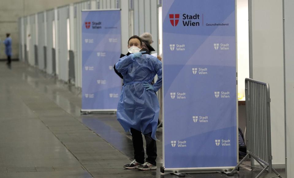 A medical worker waits for patients during start of a mass vaccination campaign against the coronavirus and the COVID-19 disease in Vienna, Austria, Friday, Jan. 15, 2021. Authorities started to vaccinate the most vulnerable people in a coordinated effort. (AP Photo/Ronald Zak)