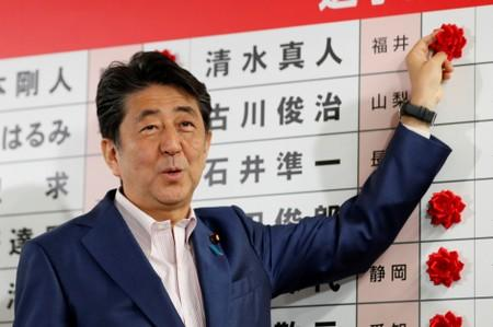 Japan's Prime Minister Shinzo Abe puts a rosette on the name of a candidate who is expected to win the upper house election at the LDP headquarters in Tokyo