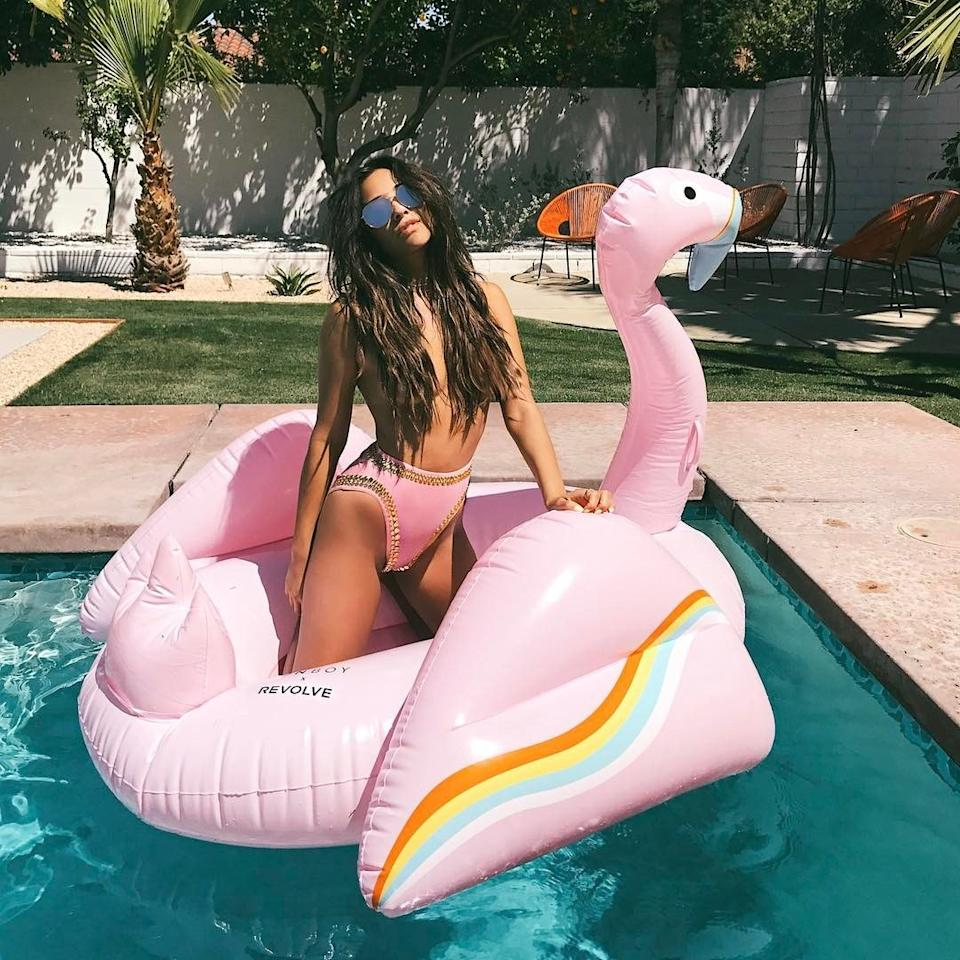 Shay Mitchell posing like a pro on a pastel pink version of the flamingo float.