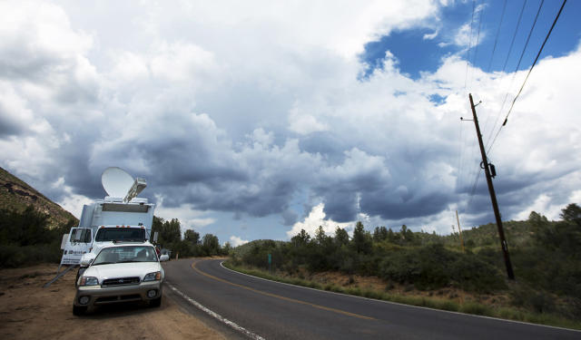 <p>Storm clouds loom over Tonto National Forest, Ariz., where rescuers are still searching for a missing 27-year-old man washed away by floodwaters, Monday, July 17, 2017. Sheriff's officials said thunderstorms and heavy rain could endanger rescuers searching upstream. A torrent of water came Saturday as people were cooling off in a creek when a rainstorm upstream unleashed floodwaters that killed nearly a dozen people. (AP Photo/Angie Wang) </p>