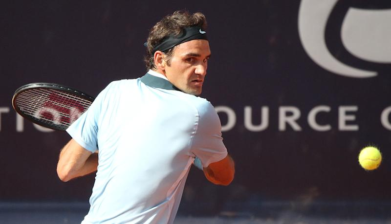 Swiss tennis player Roger Federer returns a ball to Czech Jan Hajek during their round of 16 match at the International German Open ATP tennis tournament in Hamburg, Germany, Thursday July 18, 2013. Federer won in two sets by 6-4 and 6-3. (AP Photo/dpa,Axel Heimken)