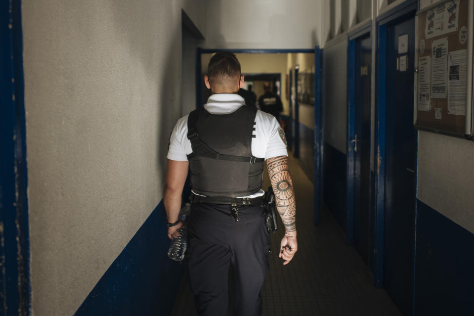 Police officer Victor walks inside the police station of the Paris suburb of Sarcelles, Tuesday, June, 15, 2021. The police station in Sarcelles was attacked in February by youths who launched noisy fireworks and threw stones, according to authorities. No injuries were reported but the attack was one of several targeting police stations that have heightened anxiety in police ranks. (AP Photo/Lewis Joly)