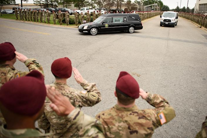 Soldiers salute as a hearse carrying the remains of Staff Sgt. Ian Paul McLaughlin drive by on Fort Bragg, N.C., on Saturday, Jan. 18, 2020. McLaughlin was killed Jan. 11 in Afghanistan.