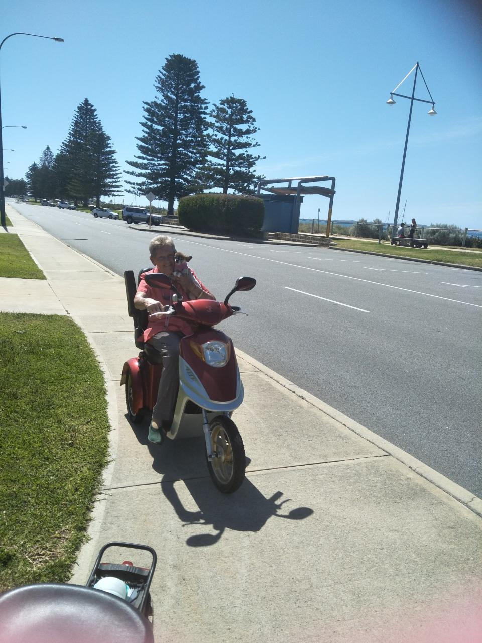 Elderly woman using mobility scooter on footpath as road rules revealed.