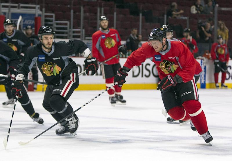 Chicago Blackhawks left wing Brandon Saad, right, skates past defenseman Niklas Hjalmarsson to get the puck during NHL hockey practice Friday, June 14, 2013, in Chicago. The Blackhawks lead the Boston Bruins 1-0 in the best-of-seven games Stanley Cup final series. Game 2 is scheduled for Saturday in Chicago.  (AP Photo/Scott Eisen)