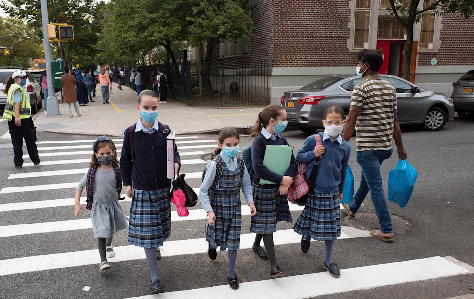 Students wearing masks walk to school in the Kensington neighborhood, Tuesday, Sept. 29, 2020 in the Brooklyn borough of New York.