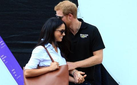 Prince Harry and Meghan Markle share a tender moment at the Invictus Games - Credit: Vaughn Ridley/Getty