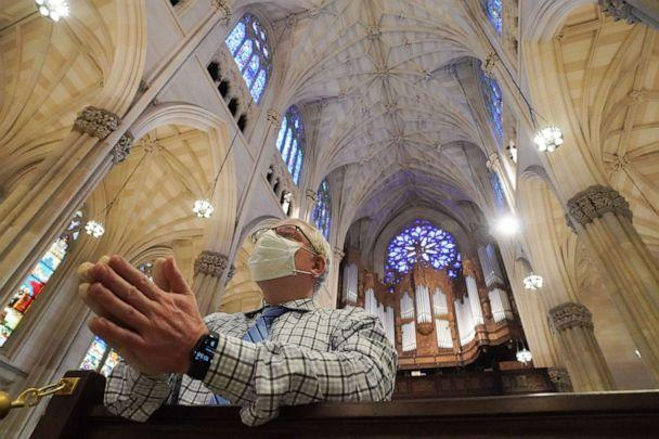 PHOTO: A man wearing a face mask prays inside St. Patrick's Cathedral in New York City as it reopens for Mass at 25% capacity amid the coronavirus pandemic on June 28, 2020. (Bryan R. Smith/AFP via Getty Images)
