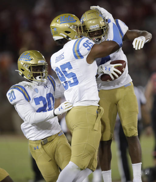 UCLA's Stephan Blaylock, right, celebrates with Jason Harris (95) after recovering a Stanford fumble during the second half of an NCAA college football game Thursday, Oct. 17, 2019, in Stanford, Calif. At left is UCLA's Elisha Guidry (20). (AP Photo/Ben Margot)