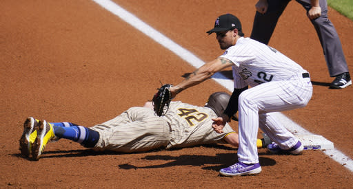 Colorado Rockies first baseman Josh Fuentes, front, fields the pickoff throw from starting pitcher Ryan Castellani as San Diego Padres' Jake Cronenworth dives back to first base in the first inning of a baseball game Sunday, Aug. 30, 2020, in Denver.(AP Photo/David Zalubowski)