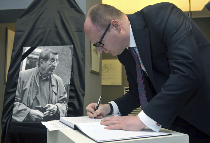 FILE - In this Monday, April 13, 2015 file photo, Pawel Adamowicz, the mayor of Gdansk, signs a condolence book in memory of German writer Guenter Grass, in Gdansk, Poland. Poland's health minister says that Gdansk Mayor Pawel Adamowicz has died from stab wounds a day after being attacked onstage by an ex-convict at a charity event, it was reported on Monday, Jan. 14, 2019. (AP Photo/ Maciej Kosycarz, File)