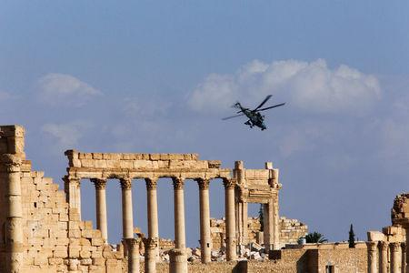A Russian helicopter flies over the Temple of Bel in the historic city of Palmyra